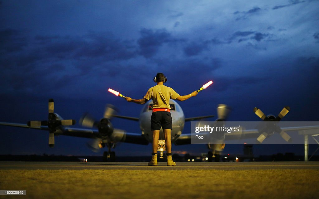A ground controller guides a Royal Australian Air Force AP3C Orion on the tarmac upon its return from a search for Malaysian Airlines flight MH370...