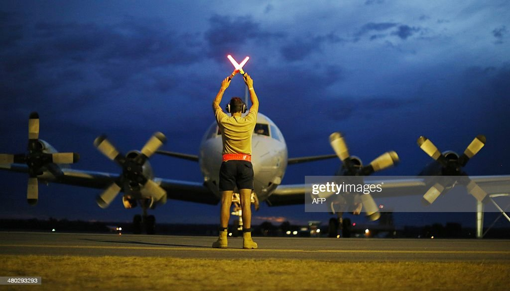 A ground controller guides a Royal Australian Air Force AP-3C Orion to rest after sunset upon its return from a search operation for the missing Malaysia Airlines flight MH370 over the Indian Ocean, at Pearce Airbase in Bullsbrook, 35 kms north of Perth on March 24, 2014. Malaysia Airlines revealed on March 24 the co-pilot of its missing jet was flying the Boeing 777 for the first time without a so-called 'check co-pilot' looking over his shoulder. AFP PHOTO/POOL/Jason REED