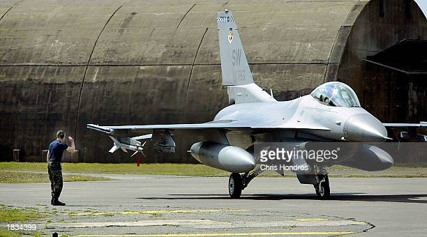 A ground controller salutes a F16 fighter jet March 7 2003 at Incirlik Air Force Base in Turkey Activity at Incirlik one of the Air Force's main...