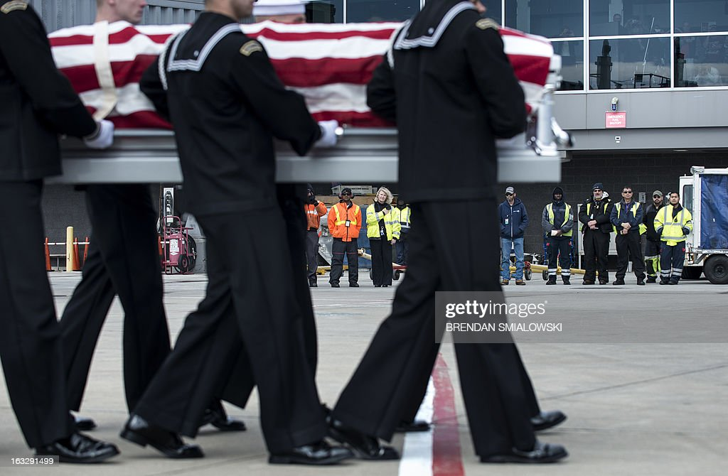 Ground crew and others watch as a US Navy transfer team carries the remains of an US Civil War (1861-1865) casualty from Delta Flight 1172 to a hearse during a dignified transfer at Dulles International Airport March 7, 2013 in Sterling, Virginia. The remains of two unknown soldiers found inside the sunken iron clad ship, the USS Monitor, were transfered for burial at Arlington National Cemetery after being discovered in 2002 and being sent to Joint POW/MIA Accounting Command in Hawaii for possible genetic identification. AFP PHOTO/Brendan SMIALOWSKI