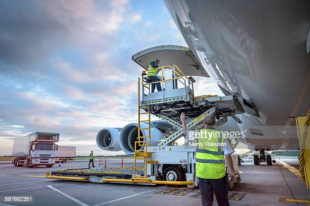 Ground crew attending to A380 aircraft with freight loader at airport