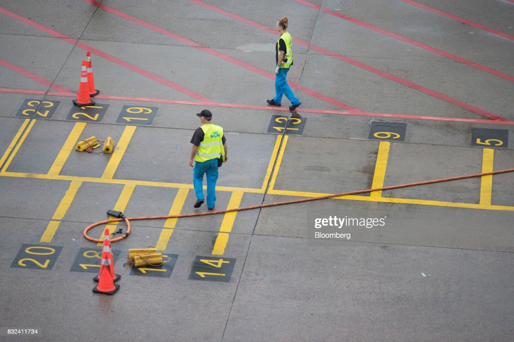 Ground crew await the arrival of a passenger aircraft operated by KLM, the Dutch arm of Air France-KLM Group, at Schiphol airport in Amsterdam, Netherlands, on Tuesday, Aug. 15, 2017. Delta Air Lines Inc., China Eastern Airlines Corp. and Air France-KLM Group are reaching for their checkbooks to forge a deeper global alliance. Photographer: Jasper Juinen/Bloomberg via Getty Images