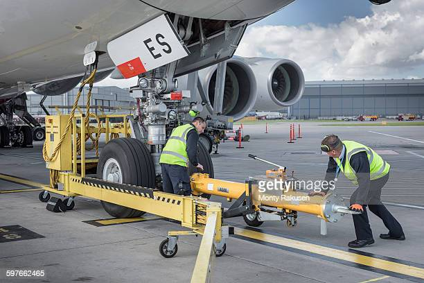 Ground crew fixing tow bar onto A380 aircraft at airport