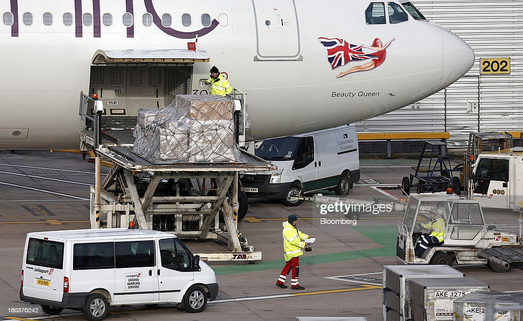 Ground crew load cargo into the hold of an Airbus A330-300 aircraft, operated by Virgin Atlantic, as it is prepared ahead of departure from terminal two at Manchester airport in Manchester, U.K., on Tuesday, Jan. 29, 2013. Manchester Airports Group, owner of Britain's busiest airport outside London, is buying Stansted from Heathrow Airport Ltd., which is ceding 100 percent of Stansted to comply with regulatory requirements. Photographer: Paul Thomas/Bloomberg via Getty Images