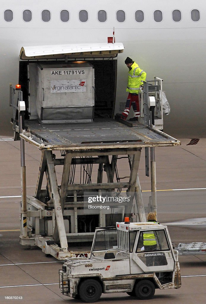 Ground crew load cargo into the hold of an Airbus A330-300 aircraft, operated by Virgin Atlantic, as it is prepared for flight at terminal two at Manchester airport in Manchester, U.K., on Tuesday, Jan. 29, 2013. Manchester Airports Group, owner of Britain's busiest airport outside London, is buying Stansted from Heathrow Airport Ltd., which is ceding 100 percent of Stansted to comply with regulatory requirements. Photographer: Paul Thomas/Bloomberg via Getty Images