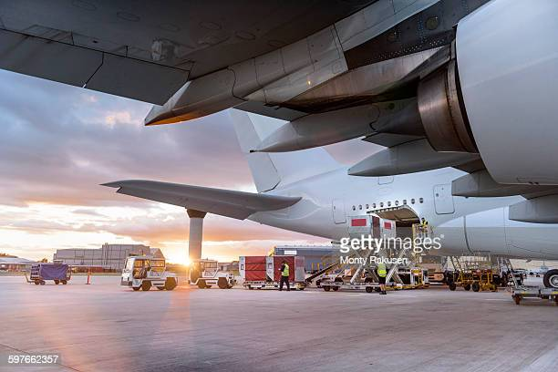 Ground crew loading A380 aircraft at sunset
