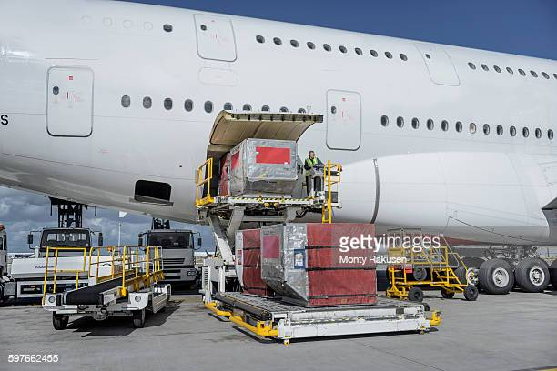 Ground crew loading freight and luggage into A380 aircraft