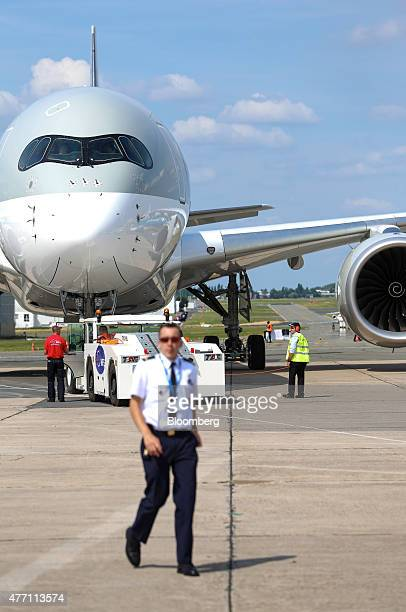 Ground crew manoeuvre an Airbus SAS A350 aircraft operated by Qatar Airways Ltd into position after landing during preparations ahead of opening at...