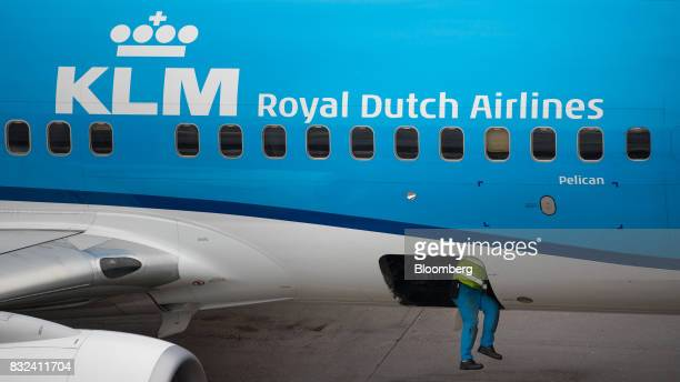 A ground crew member climbs into the cargo hold of a passenger aircraft operated by KLM the Dutch arm of Air FranceKLM Group at Schiphol airport in...