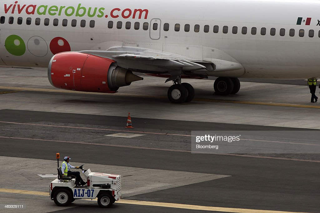 A ground crew member drives by a Grupo Viva Aerobus SAB airplane on the tarmac at Benito Juarez International Airport (AICM) in Mexico City, Mexico, on Thursday, Jan. 16, 2014. Grupo Viva Aerobus SAB filed for what would be Mexico's second initial public offering of shares by an airline since September as passenger traffic sets annual records. Photographer: Susana Gonzalez/Bloomberg via Getty Images