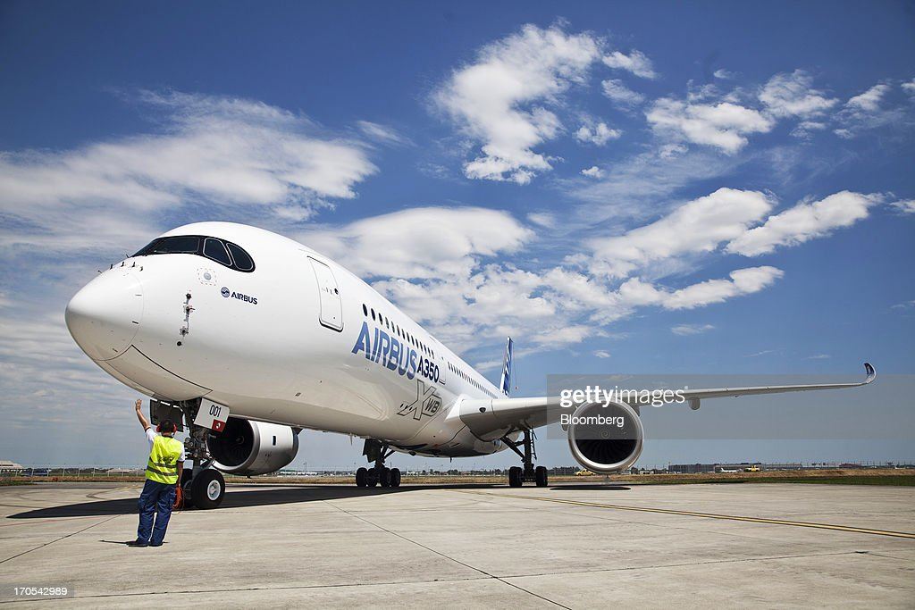 A ground crew member gestures beside an Airbus SAS A350, produced by a unit of European Aeronautic, Defence & Space Co. (EADS), as it stands on the runway following its first flight in Toulouse, France on Friday, June 14, 2013. Airbus SAS's new A350 wide-body returned from its maiden flight after a four-hour airborne test of the long-range airliner, in a show of confidence that the jet can enter service in late 2014 and challenge Boeing Co. Photographer: Balint Porneczi/Bloomberg via Getty Images