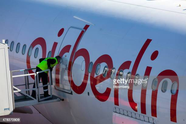 A ground crew member looks into a window of an Air Berlin aircraft at Tegel airport operated by Flughafen Berlin Brandenburg GmbH in Berlin Germany...