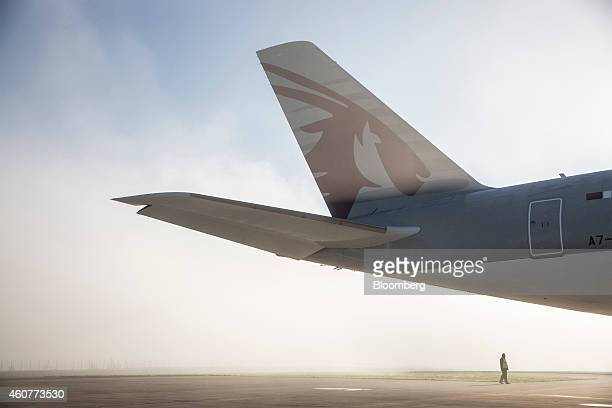 A ground crew member stands beneath the tail fin of Qatar Airways Ltd's first Airbus A350 ahead of a delivery ceremony at the Airbus Group NV factory...
