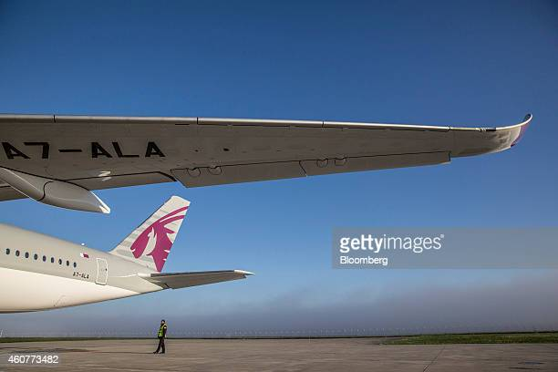 A ground crew member stands beside Qatar Airways Ltd's first Airbus A350 ahead of a delivery ceremony at the Airbus Group NV factory in Toulouse...