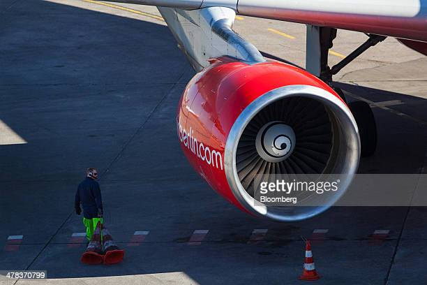 A ground crew member walks beneath an Air Berlin aircraft on the tarmac at Tegel airport operated by Flughafen Berlin Brandenburg GmbH in Berlin...