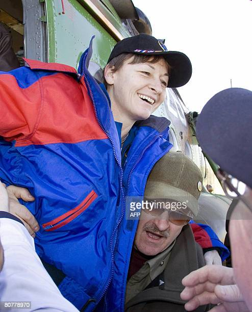 Ground crew members help US astronaut Peggy Whitson after landing in a Russian space capsule in Arkalyk northern Kazakhstan on April 19 2008 The...
