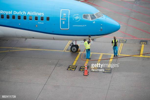 Ground crew refuel a passenger aircraft operated by KLM the Dutch arm of Air FranceKLM Group at Schiphol airport in Amsterdam Netherlands on Tuesday...