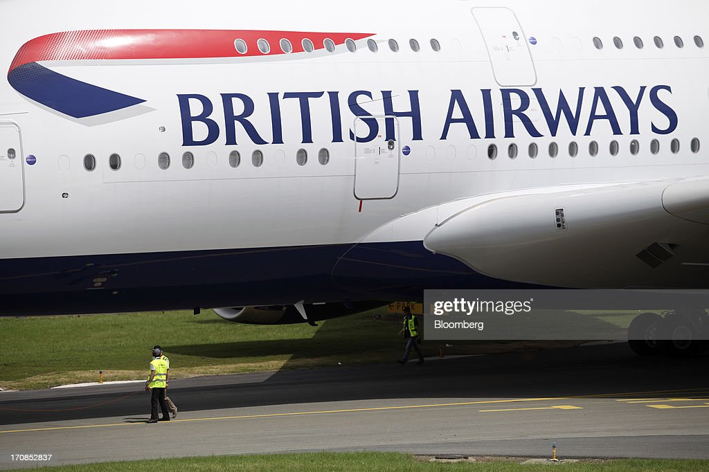 Ground crew stand beneath the fuselage of an Airbus SAS A380 aircraft, operated by British Airways, on the second day of the Paris Air Show in Paris, France, on Tuesday, June 18, 2013. The 50th International Paris Air Show is the world's largest aviation and space industry show, and takes place at Le Bourget airport June 17-23. Photographer: Balint Porneczi/Bloomberg via Getty Images