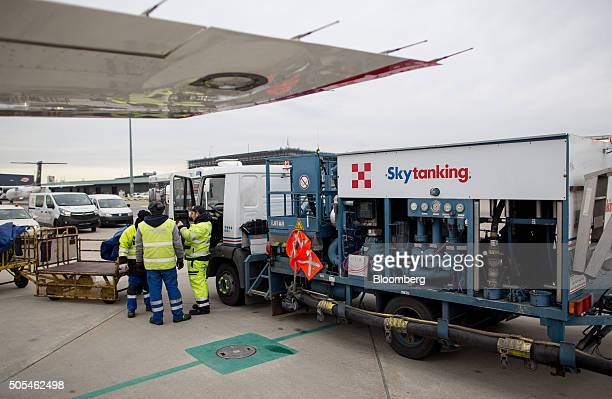 Ground crew stand beside a Skytanking fuel truck operated by Marquard Bahls AG as it sits by an aircraft at Vienna International Airport operated by...