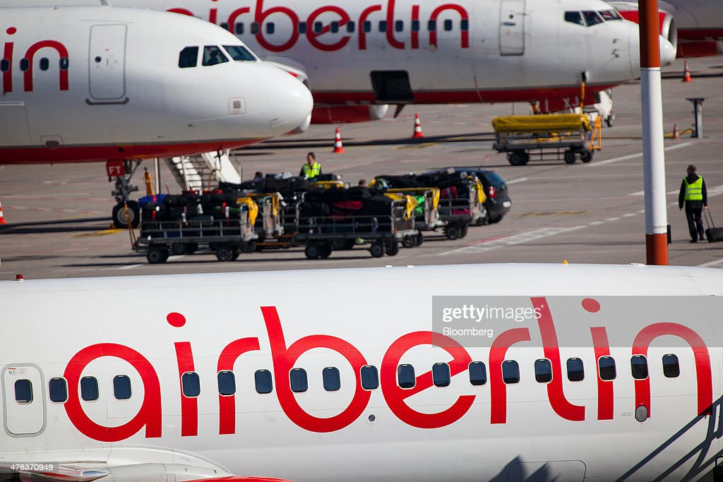 Ground crew transport passenger luggage as Air Berlin aircraft sit on the tarmac at Tegel airport, operated by Flughafen Berlin Brandenburg GmbH, in Berlin, Germany, on Wednesday, March 12, 2014. Berlin's Tegel airport has subsisted by chance alone, defying the odds as passenger growth outpaces every other major hub in Western Europe. Photographer: Krisztian Bocsi/Bloomberg via Getty Images