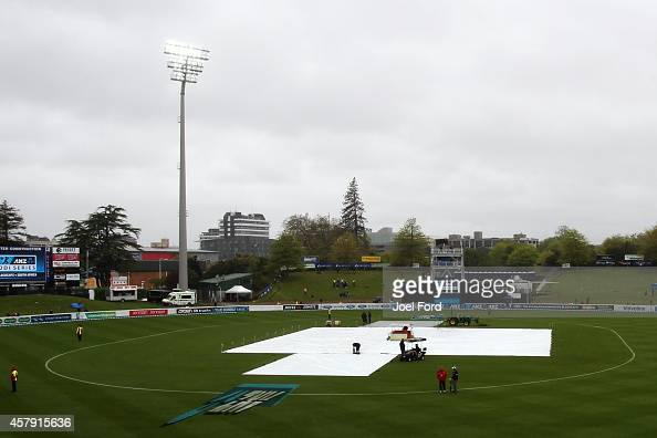 Ground crew work to cover the wicket during a rain delay during the One Day International match between New Zealand and South Africa at Seddon Park...