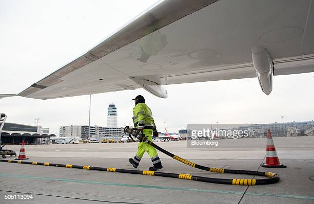 A ground crew worker carries a fuel pipe under a passenger aircraft on the tarmac at Vienna International Airport operated by Flughafen Wien AG in...