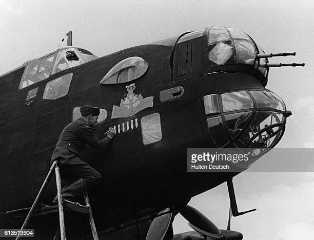 A ground crew worker of the Royal Navy paints bombs on the side of a Halifax Bomber signifying successful bombing missions