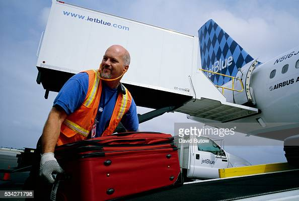 A ground crewman unloads luggage from a JetBlue flight at Long Beach Airport