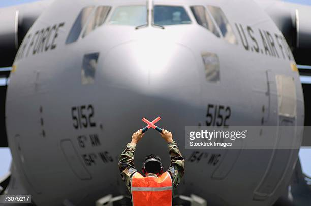 Ground crewmember marshals a C-17 Globemaster III to its parking spot at Hickam Air Force Base, Hawaii, on Wednesday, June 14.