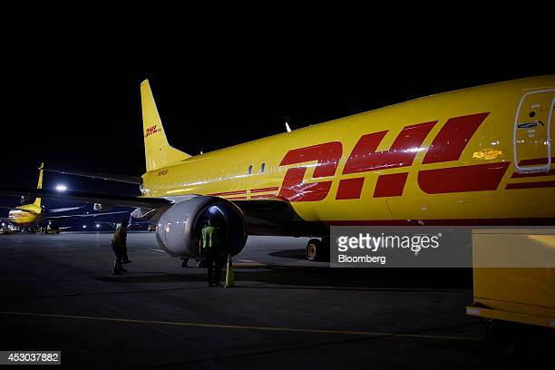 Ground crews inspect the engines on a cargo plane during the overnight sort at the DHL Worldwide Express hub of Cincinnati/Northern Kentucky...