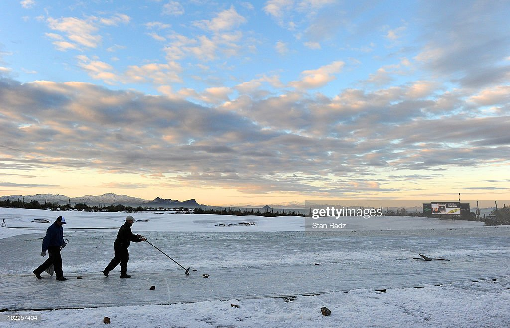 Ground crews remove snow on the driving range at sunrise before the restart of the first round of the World Golf Championships-Accenture Match Play Championship at The Golf Club at Dove Mountain on February 21, 2013 in Marana, Arizona.