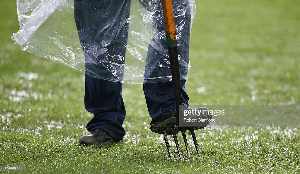 Ground keepers look to remove excess water from the pitch as heavy rain falls prior to the Barclays Asia Trophy Semi Final match between Tottenham Hotspur and Sunderland at Hong Kong Stadium on July 24, 2013 in So Kon Po, Hong Kong.