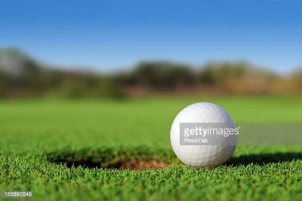 Ground level close up of golf ball close to hole