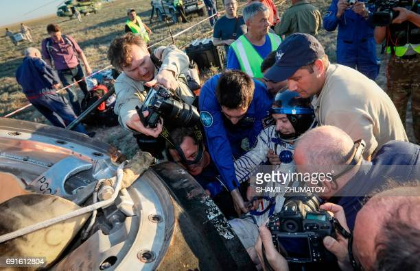 Ground personnel help French astronaut Thomas Pesquet to get out of the Soyuz MS03 space capsule after landing in a remote area outside the town of...