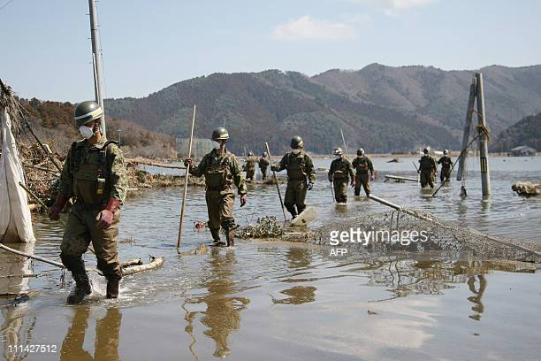 Ground Self Defense Force soldiers form a line to search for missing people in the water covered rice fields at Ishinomaki on April 1 2011 Thousands...