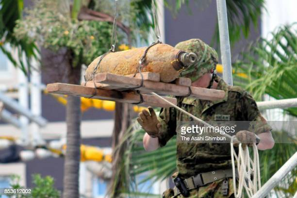 A Ground SelfDefense Force member helps to remove a defused US bomb on September 23 2017 in Naha Japan A renowned tourist destination here was...