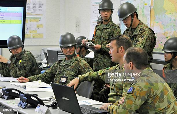 Ground SelfDefense Force officers discuss a joint training exercise with their counterparts from the United States and Australia during a joint...