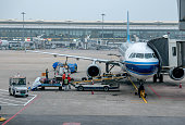 Ground service men convey luggage to a passenger plane of China Southern Airlines The year of 2015 is the most profitable year for Chinas aviation...