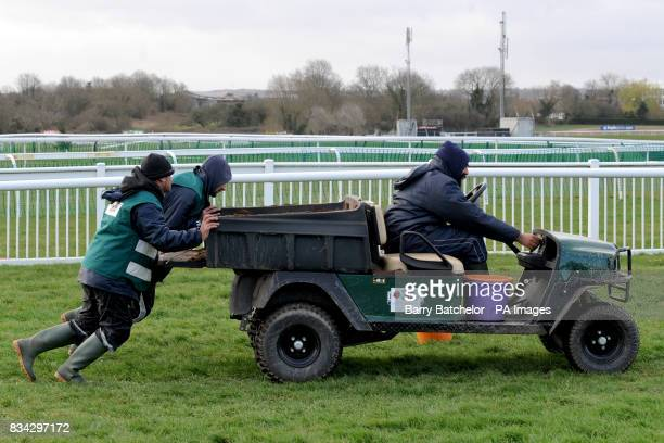 Ground Staff at Cheltenham Rcecourse help along a buggy that has bogged down during the Cheltenham Festival
