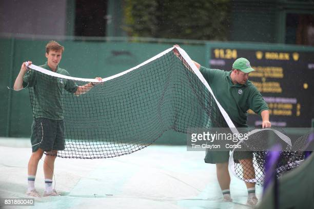 Ground staff clearing the courts of the net during a rain delay at the Wimbledon Lawn Tennis Championships held at the All England Lawn Tennis and...