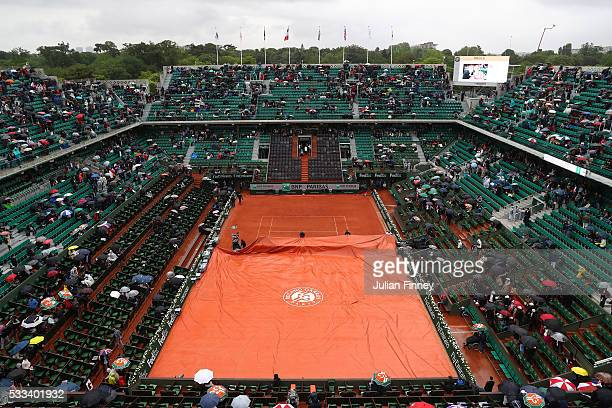 Ground staff cover court Phillipe Chartrier as rain delays play on day one of the 2016 French Open at Roland Garros on May 22 2016 in Paris France