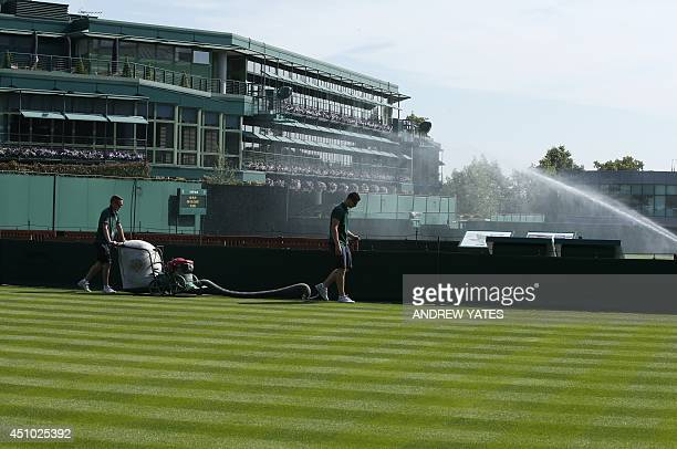 Ground staff cut the grass on a court at the All England Tennis Club in Wimbledon southwest London on June 22 on the eve of the start of the 2014...