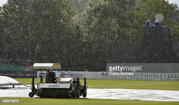 Ground staff get to work after heavy rain stops play during the ODI cricket game between Ireland and Australia at Stormont cricket ground on August...