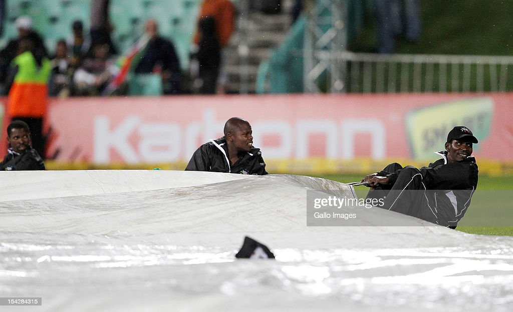 Ground staff hold the covers down in the wind storm during the Karbonn Smart CLT20 match between Kolkata Knight Riders and Perth Scorchers at Sahara Stadium Kingsmead on October 17, 2012 in Durban, South Africa.