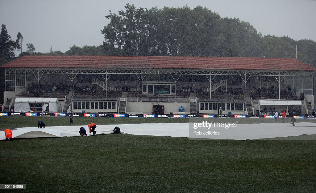 Ground staff lay covers as a wet and wild storm front hits the University Ovel Dunedin during day four of the First Test match between New Zealand...