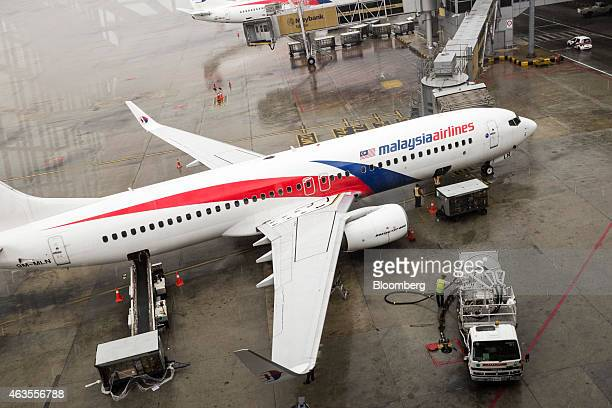 Ground staff load an aircraft operated by Malaysian Airlines System Bhd at Kuala Lumpur International Airport in Sepang Malaysia on Friday Aug 8...