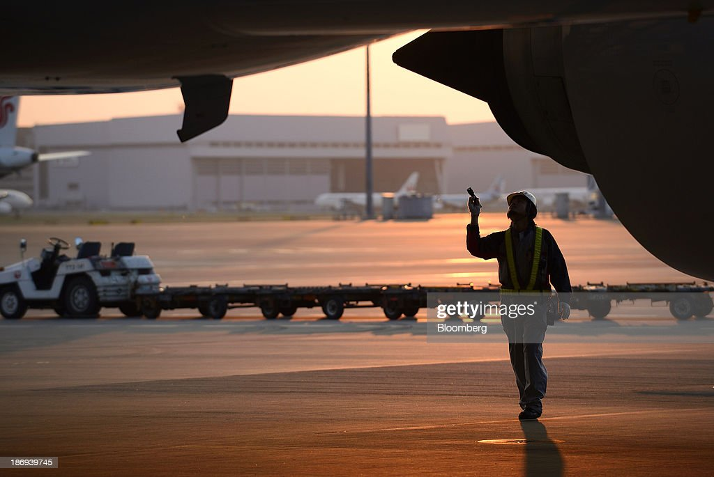 A ground staff member checks a Japan Airlines Co. (JAL) aircraft at Haneda Airport in Tokyo, Japan, on Tuesday, Nov. 5, 2013. JAL, Japan's second-largest carrier, raised its full-year profit outlook on Oct. 31 as it expects demand to increase on its Southeast Asia routes. Photographer: Akio Kon/Bloomberg via Getty Images