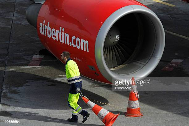 A ground staff member positions a cone around the engine of an Air Berlin passenger jet at Tegel airport in Berlin Germany on Wednesday March 23 2011...