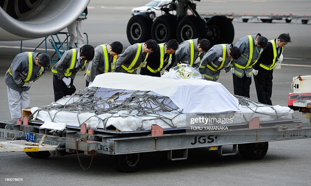 Ground staff members bow after a coffin carrying the last Japanese victim of the Algerian hostage crisis was unloaded from a plane at Narita Airport, outside Tokyo on January 26, 2013. The body of the last of 10 Japanese killed in the Algerian hostage crisis arrived in Japan by commercial flight, a day after the bodies of the nine others returned home with seven Japanese survivors. AFP PHOTO / Toru YAMANAKA