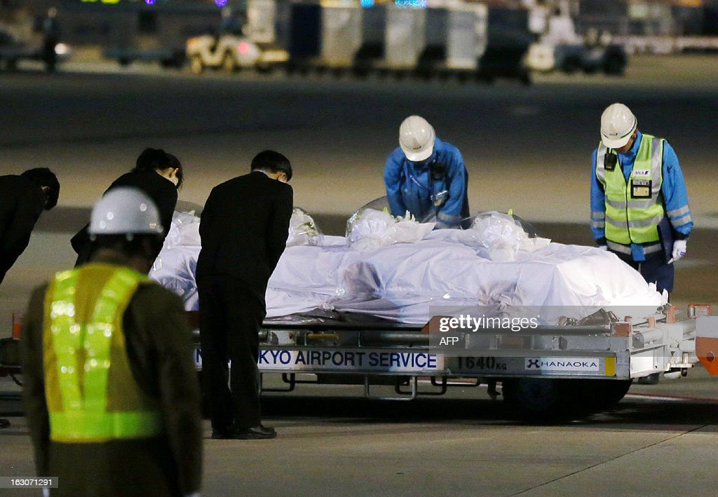 Ground staff members bow after coffins carrying victims of a hot air balloon accident in Egypt are unloaded from an air plane at the Narita international airport, suburban Tokyo on March 4, 2013. The bodies of four Japanese tourists killed in the hot air balloon accident returned from Egypt with their relatives.